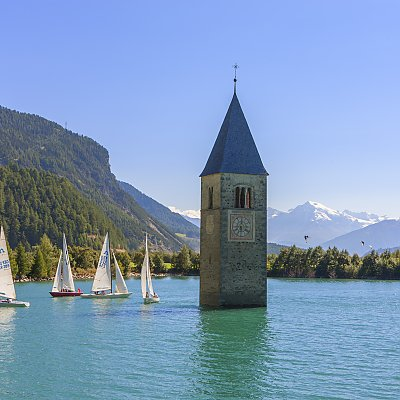 View of sailors and the church tower in the water at lake Lago di Resia
